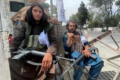 Members of Taliban forces sit at a checkpost in Kabul