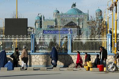 People walk in front of the Hazrat Ali or Blue Mosque in Mazar-e-Sharif