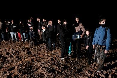 Migrants cross a field next to the Belarus-Latvia border near Vorzova