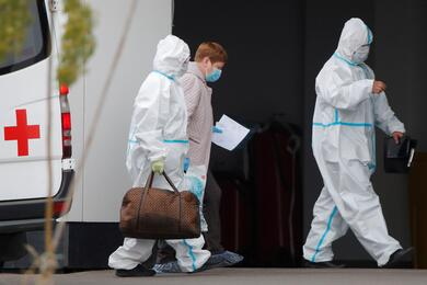 Medical specialists accompany a woman outside a hospital for patients infected with coronavirus disease in Moscow