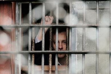 """A Belarussian detainee, arrested during the flash mob """"Revolution through a social network"""", gestures from a prison cell at a detention centre in Minsk"""
