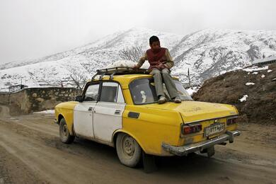 An Afghan boy sits on top of taxi as his family takes supplies of flour home in Kabul