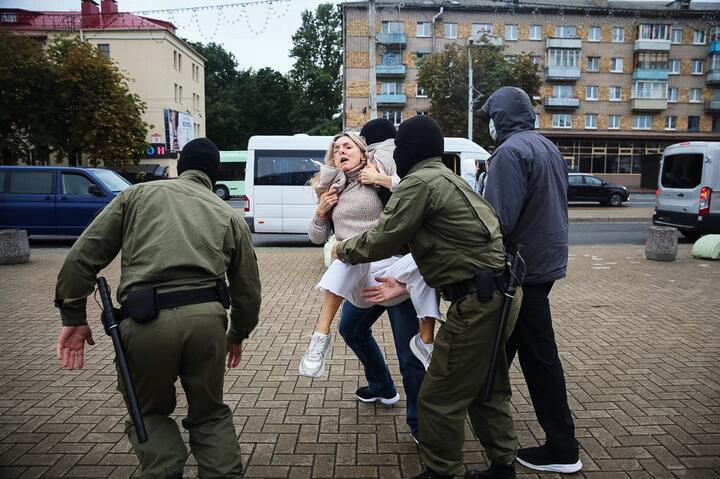 ОМОНовцы в форме оливкового цвета задерживают женщину. Минск, сентябрь 2020 года